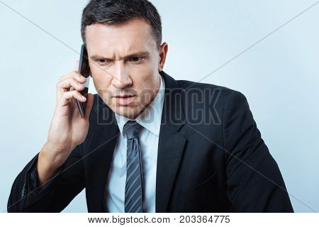 Bad news. Serious unhappy smart businessman listening to his interlocutor and showing his emotions while receiving bad news