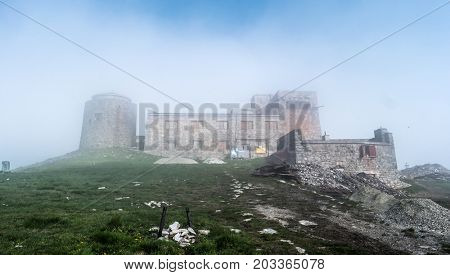 Mist mountain landscape with old abandoned observatory on mount Pip Ivan in Carpathian mountains