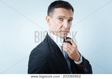 Office style. Joyful nice confident man wearing a suit and fixing his tie while getting ready to work
