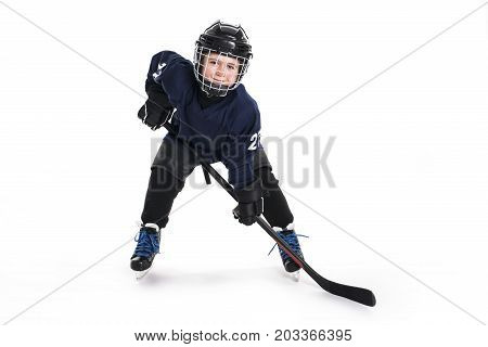 A Young boy in ice hockey gear against white