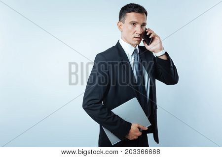 Phone communication. Serious pleasant nice talking on the phone and discussing business issues while holding a folder with document