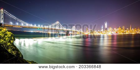 Oakland Bay Bridge In California At Night With San Francisco Skyline