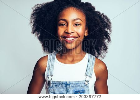 Young African Girl Smiling Happily Against A Gray Background