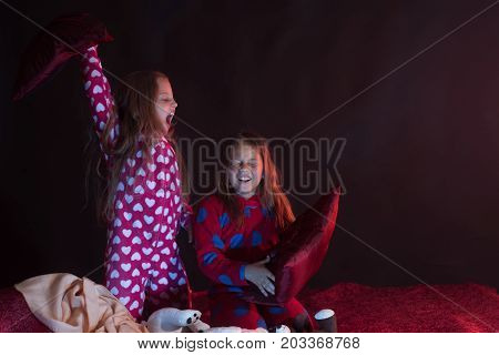 Girls With Smiling Faces Sit On Dark Red Background
