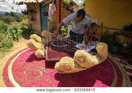 August 6 2017 Medellin Colombia: flower farmers creating floral display for the annual parade under the watchful eyes of tourists