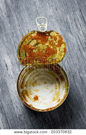high-angle shot of an open and empty can with some remains of food, on a rustic gray wooden table