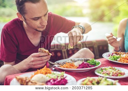 Young Man Eats Vegetables And Fish Outdoors In A Cozy Restaurant On The Water, Discover New Kitchen