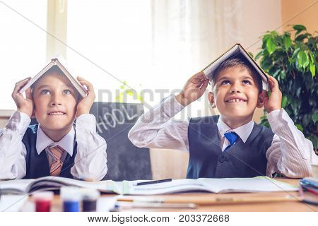 Back To School. Cute Children Sitting At The Desk In The Classroom. Boys Are Naughty And Hold The Bo