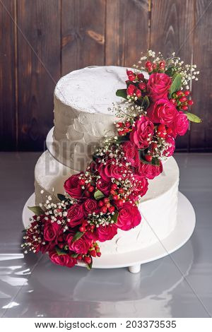A Large Tiered Wedding Cake Decorated With Red Roses On The Table