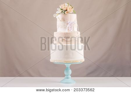 A Large Tiered Wedding Cake In The Form Of Dress With Lace Decorated With Pink Roses On Top Of The T