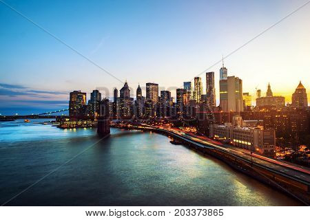 New York USA. Aerial view on the city skyline in New York City USA during the sunset. Famous skyscrapers of the concrete jungle and car traffic. Brooklyn bridge