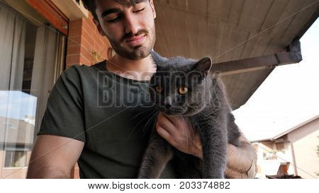 Handsome Young Animal-Lover Man Outside the House, Holding, Hugging and Petting his Gray Domestic Cat Pet.