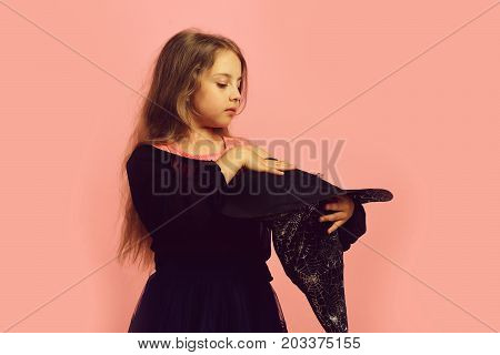 Child in witch costume and black hat. Halloween and costume party concept. Girl holds big witch cone hat isolated on pink background. Kid in holiday outfit
