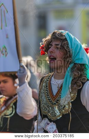 PERNIK, BULGARIA - JANUARY 27, 2017: Boy dressed in traditional female folklore costume is shouting during ritual at Surva, International Festival of the Masquerade Games
