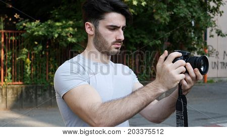 Handsome young male photographer or videomaker shooting video footage with professional photo camera