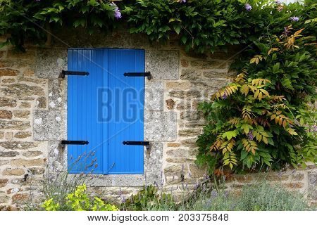 Closed blue shutters in an ancient stone building in rural france