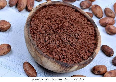 Bowl with cacao powder and beans on wooden table