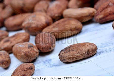 Many cacao beans on white wooden table