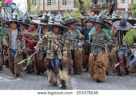 June 29 2017 Cotacachi Ecuador: kichwa indigenous men wearing chaps chanting and dancing on the street during Inti Raymi festival