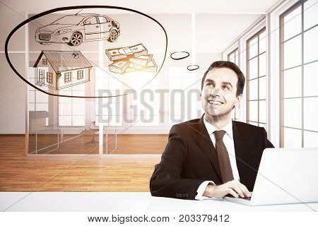 Happy young businessman in modern office using laptop and daydreaming about wealth. Rich concept
