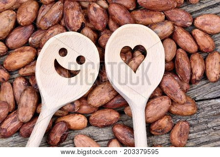 Lovely wooden spoon with cacao beans on wooden table
