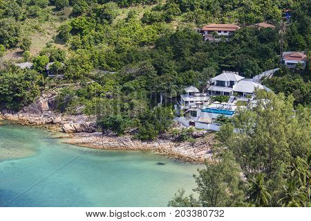 Tropical bungalow on a rocky beach next to the blue sea water. Koh Phangan Island Thailand
