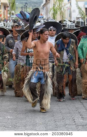June 29 2017 Cotacachi Ecuador: kichwa indigenous men with extra large hat chanting and dancing on the street during Inti Raymi festival