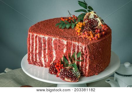 Beautiful Velvet Cake Decorated On Top With Rowan And Pomegranate On A Wooden Table. Concept Of Swee