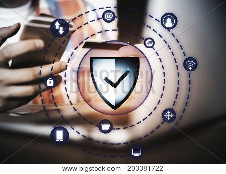 Businessman with smartphone credit card and antivirus shield hologram. Online banking concept. Double exposure