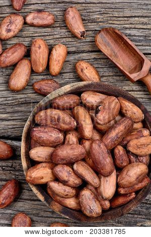 Cacao beans in a bowl on rustic wooden table