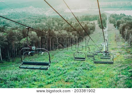 View from top of ropeway with multiple empty seats and stretched cables: green summer meadows and trees below lake Monzherok and settlement of the same name in distance Altai mountains Russia
