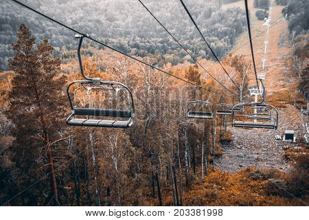 Cableway in mountains near Manzherok district of Altai mountains Russia: multiple empty seats grey and yellow forest and meadows settings below overcast evening
