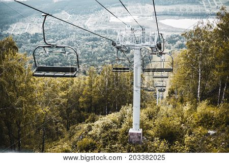 Summer landscape with working cableway surrounded by greenery with most seats empty Manzherok lake and settlement in background Altai mountains Russia