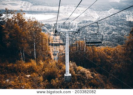 Beautiful autumn scenery from high point with empty cableway surrounded by orange and yellow dry trees and grasses below; Manzherok lake and settlement in background Altai mountains Russia