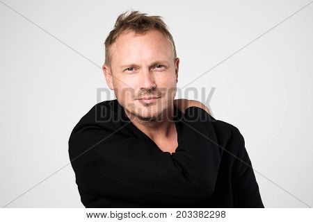 Caucasian young man in black clothes standing against white background. Concept of self confident man. Positive man emotion