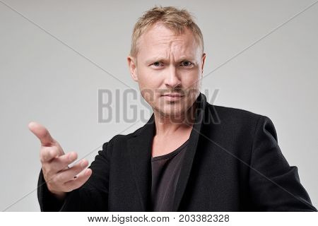 A young man with disheveled hair and black clothes looks at the camera in displeasure. He wrinkles his forehead showing displeasure and strechs hand. Concept of claim emotion poster