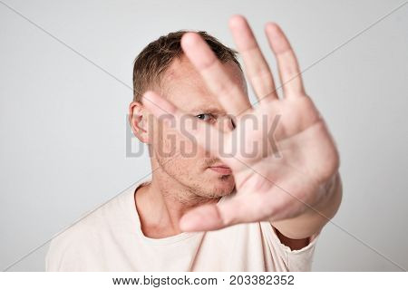 Young Caucasian man hiding his face with hand. Try to move problems away