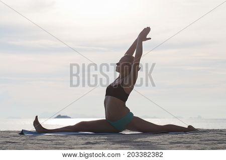 Happy young woman practicing yoga on the beach at sunset. Healthy active lifestyle concept