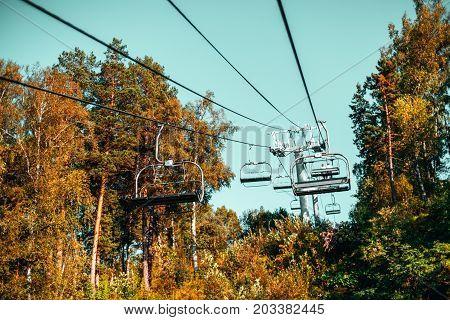 View of cableway stretching up over beautiful autumn hills and meadows with most of seats empty and couple sitting on distant one teal clean sky Russia Altai mountains Manzherok district