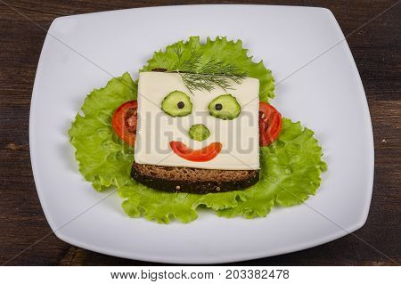 Fun food for kids - face on bread made from cheese lettuce tomato cucumber and pepper. Close up