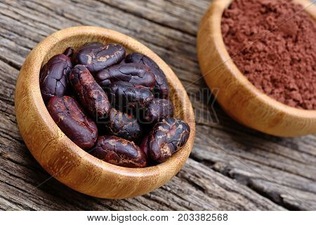 Cacao beans with powder in a bamboo bowls on wooden table