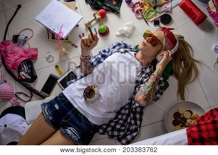 Young blonde woman lying on the floor with a cigarette in his hand and listens to music after school. Women's room, a mess, lingerie