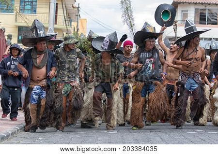 June 29 2017 Cotacachi Ecuador: kichwa indigenous people wearing furry chaps and large hats dancing on the street during Inti Raymi festival