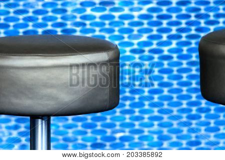 Modern black leather barstool in front of blurred vigorous blue small tile background close-up