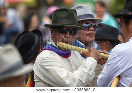 June 24 2017 Cotacachi Ecuador: indigenous kichwa man playing a flute at the Inti Raymi parade at summer solstice