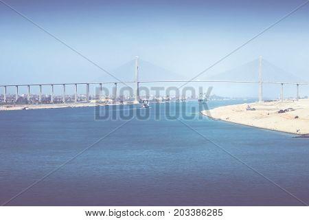 The Suez Canal at El-Qantara with ships and Mubarak Peace Bridge in hazy sunlight