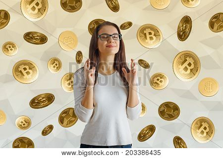 Hopeful young woman with crossed fingers on abstract background with falling coins. Lottery win and cryptocurrency concept
