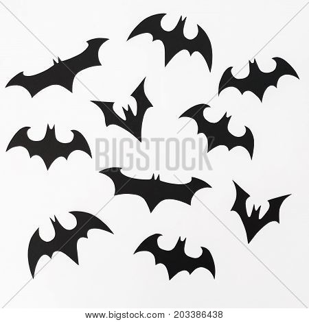Halloween pattern made of handmade black paper bats for Halloween holiday on white background. Flat lay, top view.