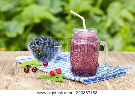Healthy eating food dieting and vegetarian concept - smoothie from blueberry raspberry cherry and banana in mug close up in nature