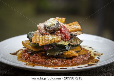 Vegetable stack - pumpkin zucchini red capsicum eggplant and mushroom cooked in a tomato onion and garlic sauce topped with parmesan cheese . Close up